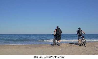 Mountain biking on summer beach - Couple of travelers ride...