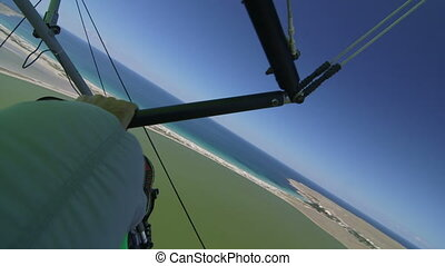 Hang-gliding over coast - Motorized hang glider flying above...