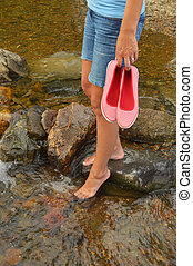 Wading in Creek - Young woman with shoes in hand, cooling...
