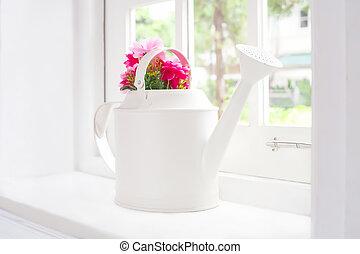 flowers in watering pot beside window