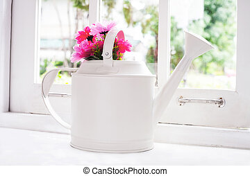 flowers in watering pot beside window