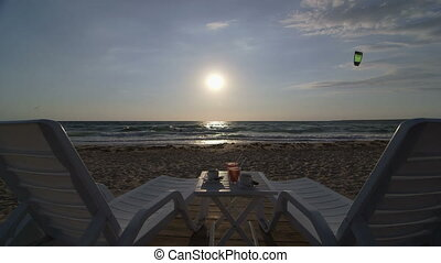 Lounge on summer beach at sunset - Two loungers, table with...