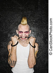 Punk biting handcuffs - Mid-adult Caucasian male punk biting...