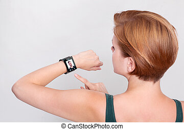 Girl with a modern Internet Smart Watch on grey background...