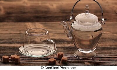 Blooming green tea in glass teapot on a vintage wooden table