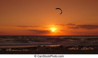 Kite surfer riding wave at sunset
