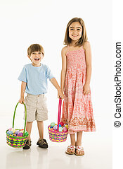Children with Easter baskets - Smiling girl and boy standing...