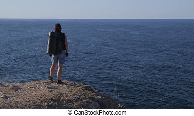 Woman with backpack on cliff by sea