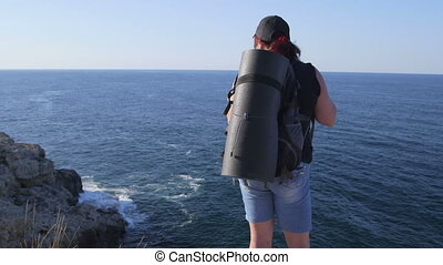 Tourist with backpack standing on rock by sea