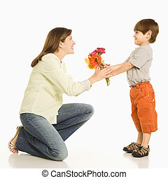 Boy giving mother flowers - Son giving bouquet of flowers to...