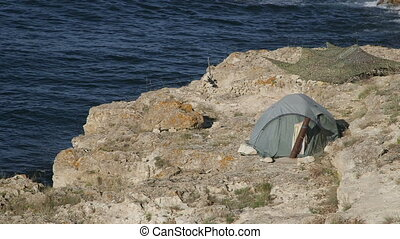 Tourist tent on rock by sea