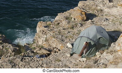 Tourist tent on a rock by the sea