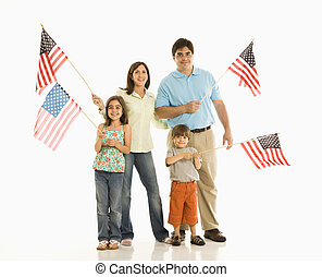 Family holding American flags. - Hispanic family holding...