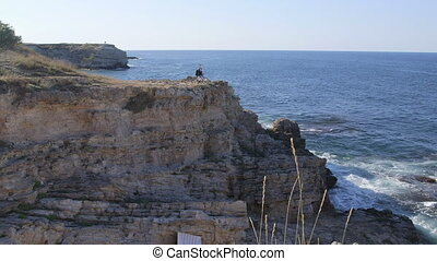 Female traveler with bicycle on cliff by sea