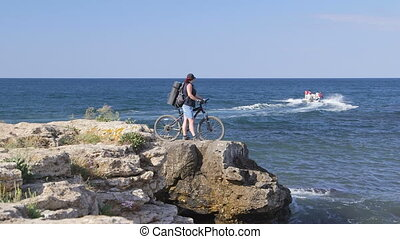 Woman With Bicycle on Rocky Beach