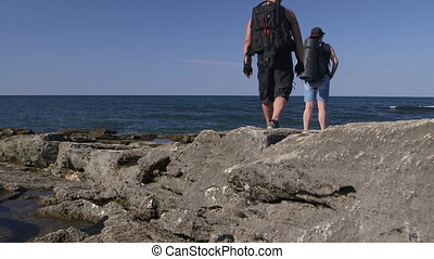 Cyclists with Backpacks on Rocky Beach