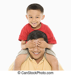 Boy on father\'s shoulders. - Asian boy sitting on father\'s...