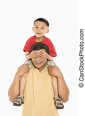Boy on dad\'s shoulders. - Asian boy sitting on father\'s...