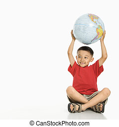 Boy holding globe. - Asian boy sitting on floor holding...
