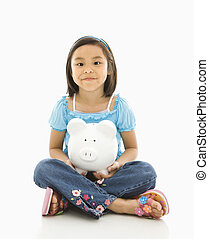 Girl holding piggybank. - Asian girl sitting on floor...