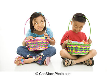 Children with Easter baskets - Asian girl and boy sitting on...