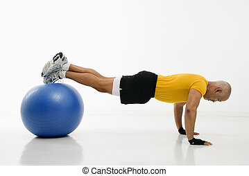 Man doing pushups. - Side view of mid adult multiethnic man...