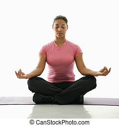 Woman practicing yoga - Mid adult multiethnic woman sitting...