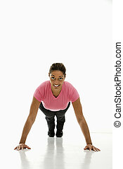 Woman doing pushups. - Mid adult multiethnic woman wearing...