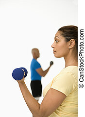 Woman exercising with dumbbell - Close up of smiling mid...