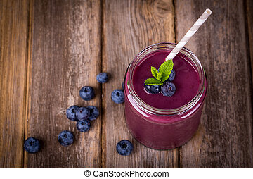 Blueberry smoothie in a glass jar with a straw and sprig of...