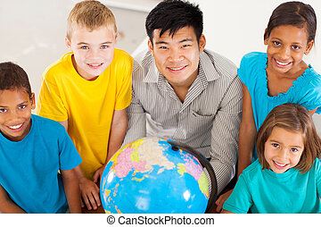 geography teacher with group of primary students - smiling...
