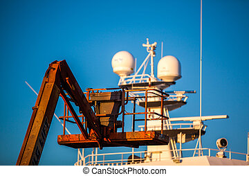 orange hoisting crane with a cage at a harbor with a white...