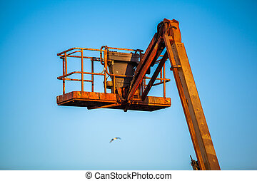 orange hoisting crane with a cage