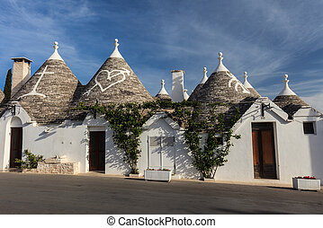 Alberobello, Italy - Trulli houses with painted symbols on...