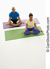 Two people practicing yoga. - Mid adult multiethnic man and...