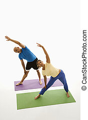 Man and woman stretching. - Mid adult multiethnic man and...