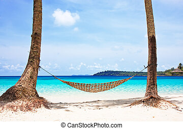Hammock between palm trees on beautiful tropical beach