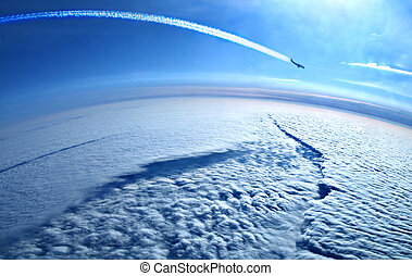Airplane contrails in the blue sky above the clouds