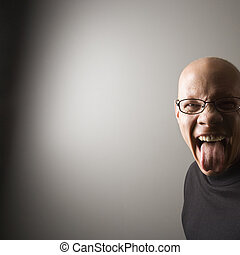 Man sticking out tongue - Portrait of mid-adult Caucasian...
