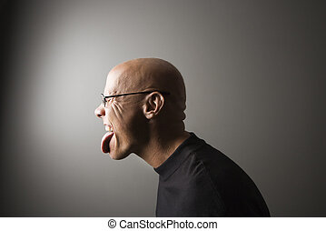 Man sticking out tongue. - Profile portrait of mid-adult...