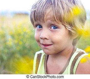 little boy in flowers field