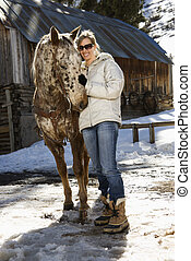 Woman petting horse. - Young adult Caucasian woman petting...