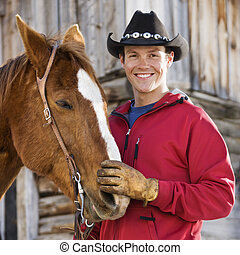 Man petting horse. - Young Caucasian man in cowboy hat...