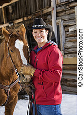 Man petting horse. - Young adult Caucasian male in cowboy...
