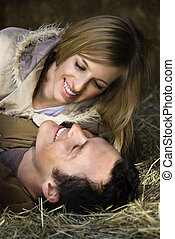 Couple lying in hay.