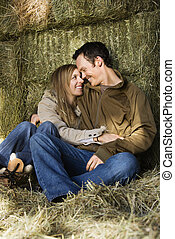 Snuggling couple in hay.