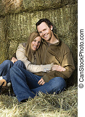 Hugging couple in hay.