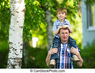 Portrait of father and son outdoors.