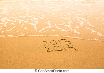 2013 - 2014 - written in sand on beach texture - soft wave of the sea.
