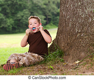 Child eating ice cream treat outdoors on hot summer day